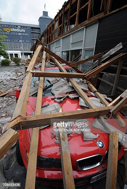 A luxury car is damaged by falling debris outside the AMI Stadium one of the 2011 Rugby World Cup venues on February 26 2011 after a 63 earthquake...