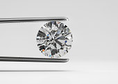 Luxury perfect shaped diamond in tweezers closeup with bright background