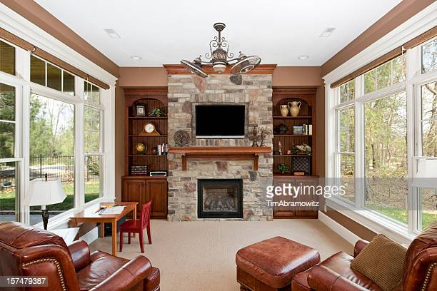 Luxury family room with stone fireplace and window walls