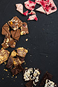 Crashed handcrafted chocolate with nuts, cookie, biscuit crumb, raspberry toppings on black background. Top view