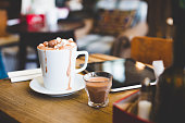 A cup of hot chocolate sits on a table next to a digital laptop. Topped with marshmallows and chocolate balls ready to be drank. A spoon lays on a napkin at the side. A shot glass with extra hot choco