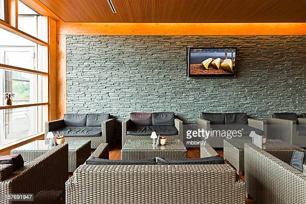 lobby do hotel de luxo com tabelas, sofás e LCD TV