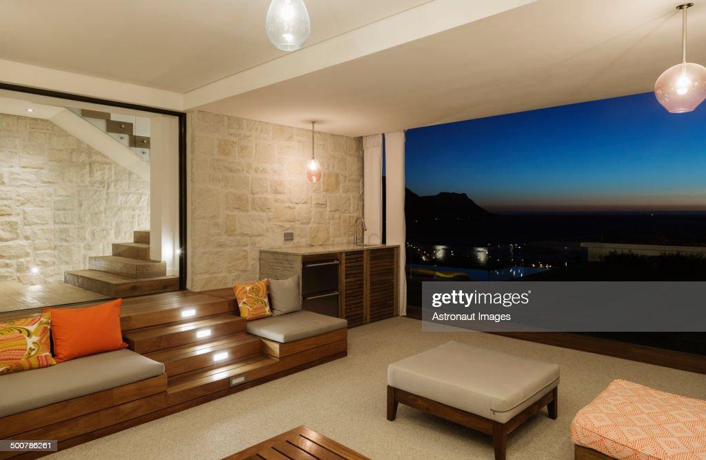 Modern Living Room With Balcony Illuminated At Night Stock Photo