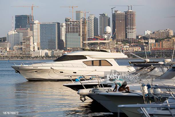Luxury motor yachts sit at their harbor moorings in Ilha district beyond the city center skyline in Luanda Angola on Saturday Nov 9 2013 Angola the...
