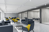 Corridor of a luxury office with dark gray and white plank walls, a concrete floor and yellow and gray armchairs standing next to gray sofas. A side view. 3d rendering