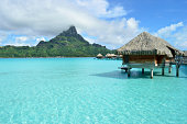 Luxury overwater thatched roof honeymoon bungalow in a vacation resort in the clear blue lagoon with a view on Mt. Otemanu and the tropical island of Bora Bora, near Tahiti, in pacific French Polynesi