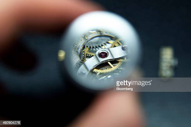 A luxury pocket watch mechanism is enlarged through a watchmakers magnifying eye loop at the Patek Philippe SA headquarters and manufacturing...