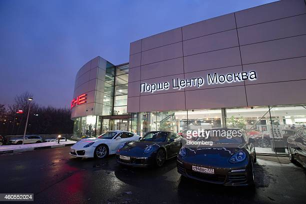 Luxury Porsche sportscars sit in the parking lot outside a Porsche AG luxury automobile dealership in Moscow Russia on Monday Dec 15 2014 Russia's...