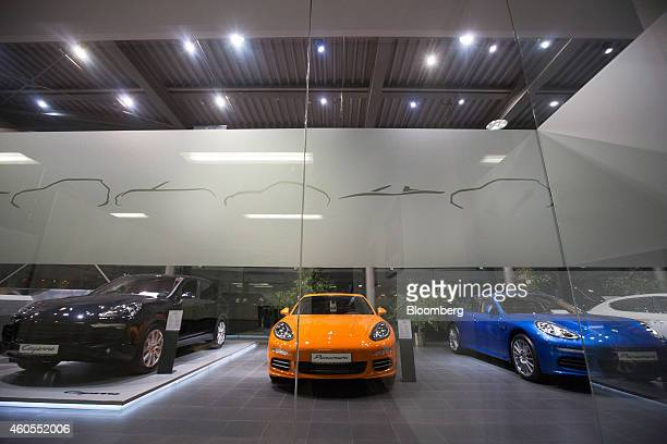 Luxury Porsche vehicles including a Porsche Cayenne left and Panamera models sit on display in the window of a Porsche AG luxury automobile...