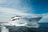A luxury private motor yacht under way on tropical sea with bow wave