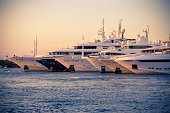 Luxury Yachts moored in a harbor of Porto Cervo on the early sunset, Sardinia, Italy