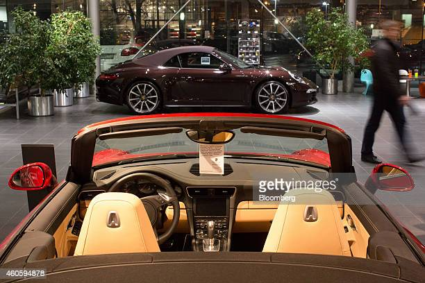 Luxury sporstcars including a Porsche 911 top sit on display inside a Porsche AG luxury automobile dealership in Moscow Russia on Monday Dec 15 2014...