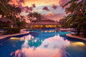 stunning caribbean sunset on a pool surrounded of palm trees