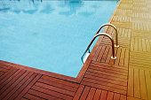 The corner view of a luxury swimming pool and its stairs with a wooden decking around.