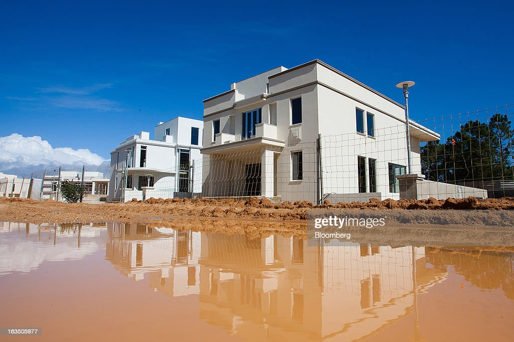Luxury villas stand near a waterlogged construction site at 'The Keys' development at Quinta do Lago in Almancil, Algarve region, Portugal, on Saturday, March 9, 2013. The tourism and real estate sector's recovery is crucial for Portugal's economy, which the government projects will return to growth next year, after shrinking an estimated 1 percent in 2013 and 3 percent in 2012. Photographer: Mario Proenca/Bloomberg via Getty Images