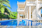 Luxury white house  with swimming pool. Luxury villa in classical style with columns.  Backyard with swimming pool in mansion.