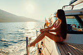 luxury woman yachting in sea at sunset. Sea waves background.
