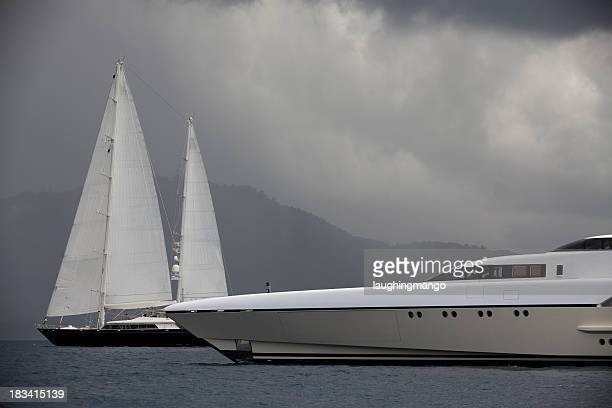 Luxury yacht and sailboats before a cloudy sky