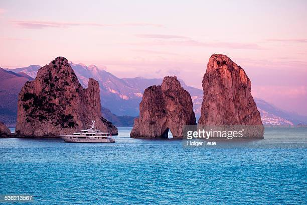 Luxury yacht near Faraglioni Rocks at sunset