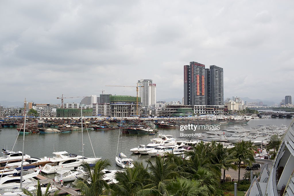 Luxury yachts sit docked at the Visun Royal Yacht Club in front of fishing boats and residential developments in the Sanya Bay district of Sanya, Hainan Province, China, on Monday, April 7, 2014. The yuan is poised to recover from declines that have made it Asia's worst-performing currency as China seeks to prevent an exodus of capital that would threaten economic growth, according to the most accurate forecasters. Photographer: Brent Lewin/Bloomberg via Getty Images