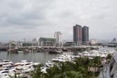 Luxury yachts sit docked at the Visun Royal Yacht Club in front of fishing boats and residential developments in the Sanya Bay district of Sanya...