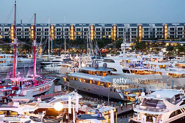 Luxury yachts sit moored at the Singapore Yacht Show in front of residential buildings of Sentosa Cove in Singapore on Thursday April 10 2014 The...