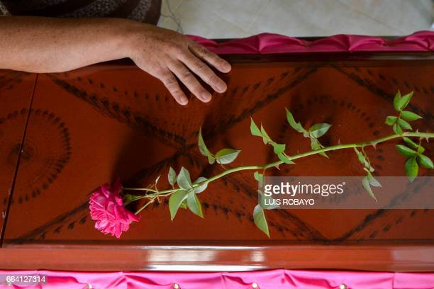 Luz Mary Ruiz mother of Deisy Rosero touches her daughter's coffin during her funeral at a cemetery in Mocoa Putumayo department southern Colombia on...