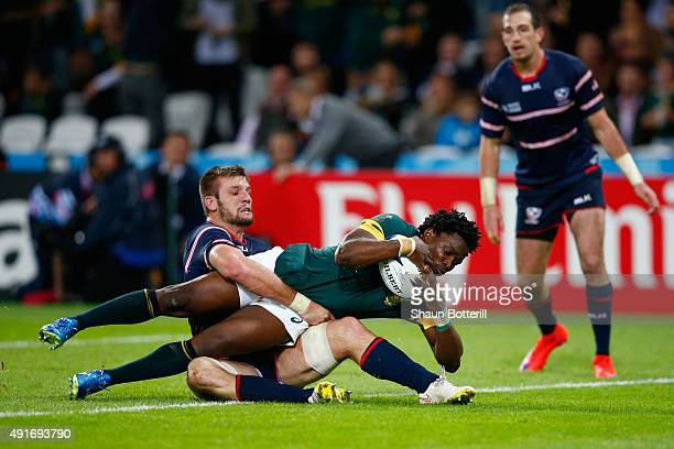 Lwazi Mvovo of South Africa goes over to score their tenth try as he is tackled by Cam Dolan of the United States during the 2015 Rugby World Cup...
