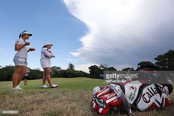 Lydia Ko of New Zealand and hitting partner Ariya Jutanugarn of Thailand wait for a buggy on the 9th hole after being told by officials that play is...