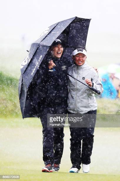 Lydia Ko of New Zealand and Megan Khang of USA shelter under an umbrella as play is called off due to lightning during day four of the New Zealand...