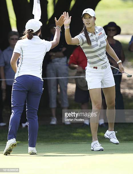 Lydia Ko of New Zealand receives a high five by Michelle Wie of the United States after scoring an eagle on the par 5 15th hole during day one of the...