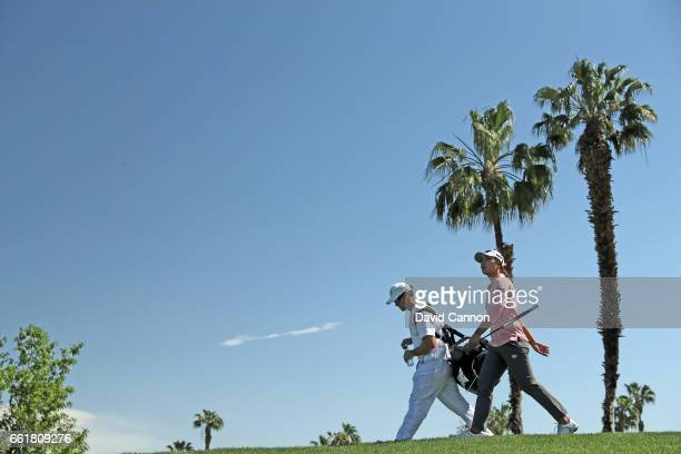 Lydia Ko of New Zealand walks from the tee on the par 3 fifth hole with her caddie Gary Matthews during the completion of the delayed first round of...