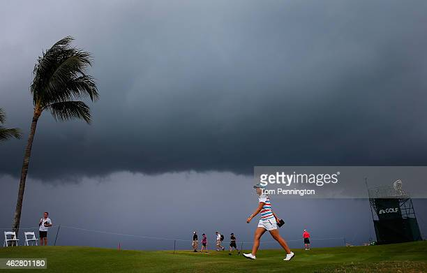 Lydia Ko of New Zealand walks to the 18th tee as a storm approaches during round one of the Pure Silk Bahamas LPGA Classic at the Ocean Club course...