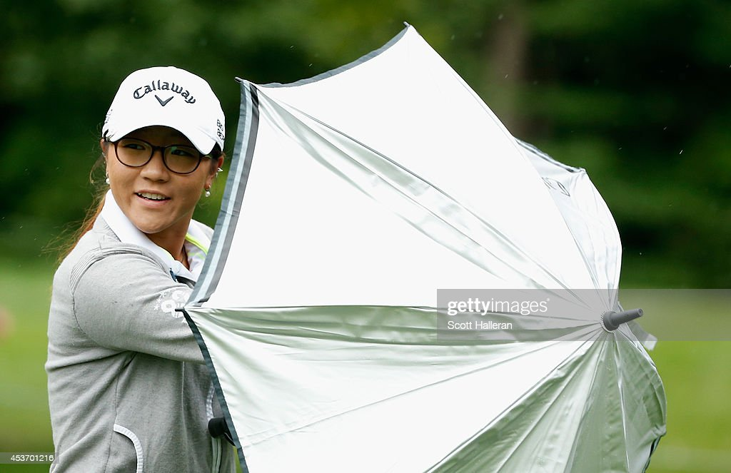 Lydia Ko of New Zealand walks under an umbrella on the seventh hole during the third round of the Wegmans LPGA Championship at Monroe Golf Club on August 16, 2014 in Pittsford, New York.