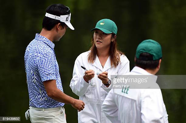 Lydia Ko signs an autograph as Kevin Na of the United States looks on during the Par 3 Contest prior to the start of the 2016 Masters Tournament at...