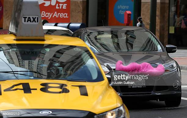 Lyft car drives next to a taxi on June 12 2014 in San Francisco California The California Public Utilities Commission is cracking down on ride...