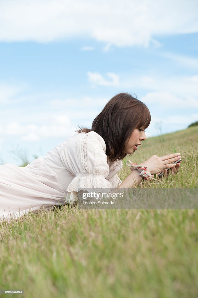 A lying girl touching the tablet PC : Stock Photo