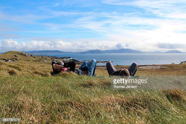 Lying in the grass and enoying the view of the rugged landscape around Malin Head, Ireland
