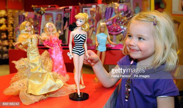 Lyla Mulcahy with a copy of the original 1959 Barbie doll in a zebra swimsuit with other Barbies from the past five decades at Hamleys toy store in...