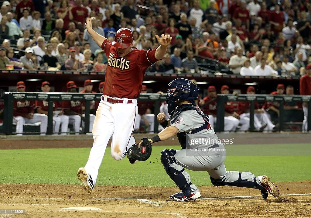 Lyle Overbay #37 of the Arizona Diamondbacks is tagged out at home plate by catcher Tony Cruz #48 of the St Louis Cardinals as he attempts to score during the fourth inning of the MLB game at Chase Field on May 9, 2012 in Phoenix, Arizona.