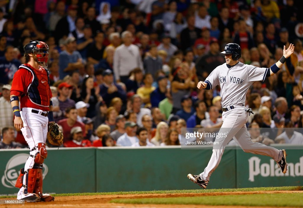 Lyle Overbay #55 of the New York Yankees reacts upon scoring in the 7th inning in front of Jarrod Saltalamacchia #39 of the Boston Red Sox during the game on September 13, 2013 at Fenway Park in Boston, Massachusetts.