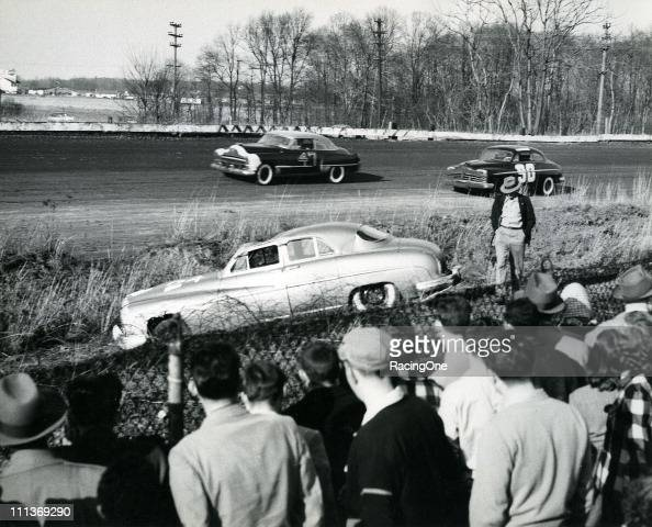 Lyle ScottÕs Lincoln sits off the racing surface after rolling over during a NASCAR Cup race at Langhorne Speedway Paul Parks and Frank Mundy pass...