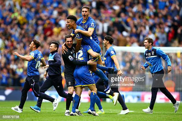 Lyle Taylor of Wimbledon celebrates with his teammates after the final whistle as they win the Sky Bet League Two Play Off Final match between...