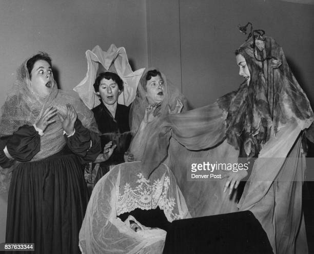 Lynda Watkins the Black Fairy throws a Curse on the new born princess while three other fairies look on in children's theater production Credit...