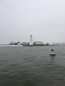 Lynde point lighthouse in Old Saybrook Connecticut in December while it lightly snows.