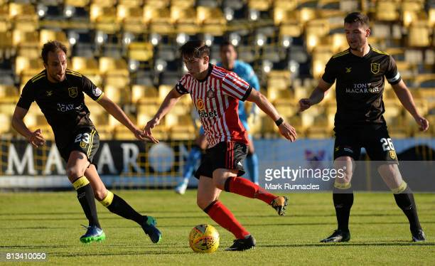 Lynden Gooch of Sunderland is challenged by Craig Halkett and Raffaele De Vita of Livingston during the pre season friendly between Livingston and...