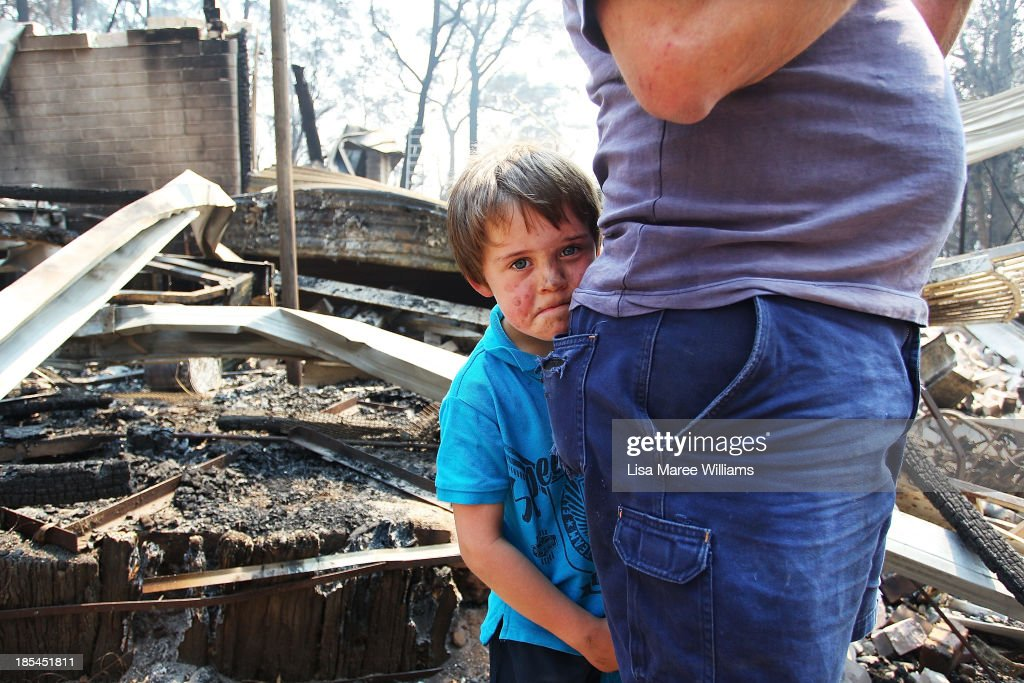 Lyndon Dunlop stands by his father as they inspect the damage to his grandparent's home of 41 years destroyed by bushfire on October 21, 2013 in Winmalee, Australia. One man has died and hundreds of properties have been destroyed in bushfires that are devastating the Blue Mountains and Central Coast regions of New South Wales.