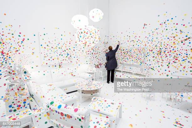 Lynley Ogilvie puts up stickers in the Obliteration Room at the Yayoi Kusama Infinity Mirrors exhibit at the Hirshhorn Museum and Sculpture Garden on...