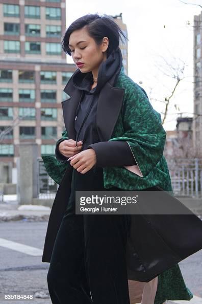 Lynn Kim Do is seen at Spring Studios outside the Phillip Lim show wearing green silk thifted kimono black neoprene three quarter length coat with...