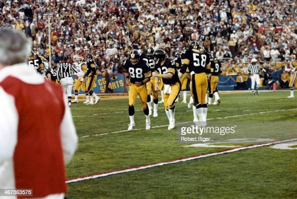 Lynn Swann of the Pittsburgh Steelers runs off the field as quarterback Terry Bradshaw celebrates during Super Bowl XIV against the Los Angeles Rams...
